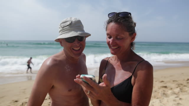 Mature couple smiling, laughing and looking at photos on cell phone at the beach in the South of France.