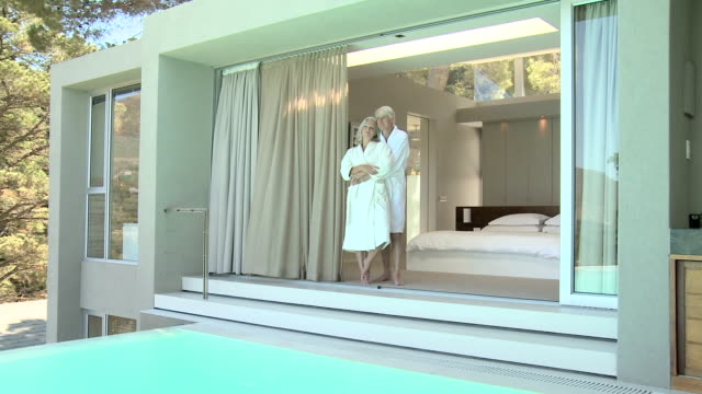 Mature couple standing at doorway of luxury house with pool