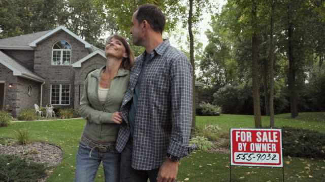 MS Mature couple standing in front of house with for sale sign / Neenah, Wisconsin, USA