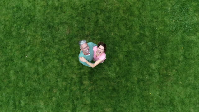 Mature couple standing on green lawn smiling up towards camera and waving