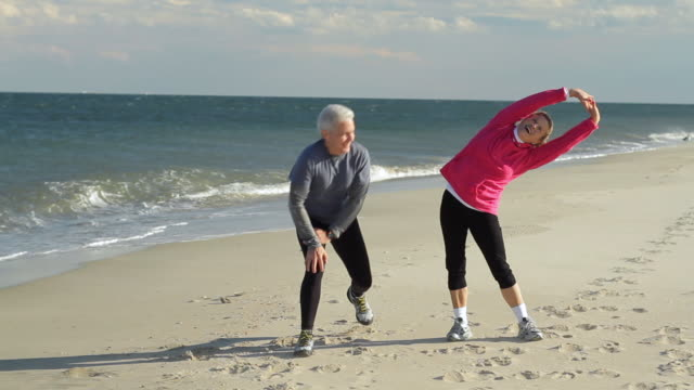 WS Mature couple stretching before run on beach / Sea Bright, New Jersey, USA