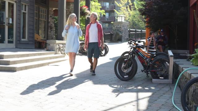 vídeos de stock e filmes b-roll de mature couple stroll village streets, past bikes - calções