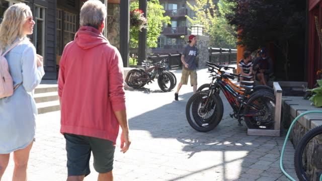 vídeos y material grabado en eventos de stock de pareja madura paseando por las calles del pueblo, bicicletas pasadas - pantalón corto