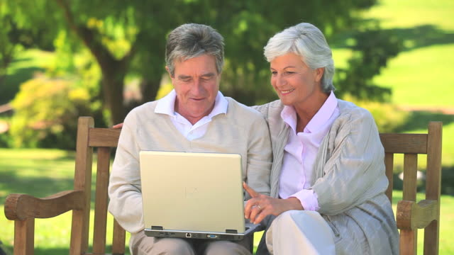 vídeos de stock, filmes e b-roll de mature couple surfing on their laptop oudoors / cape town, western cape, south africa - idoso na internet