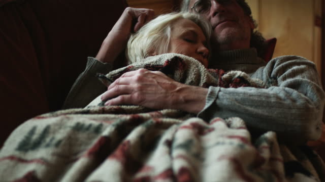 mature couple taking a nap on the couch together - blanket stock videos & royalty-free footage