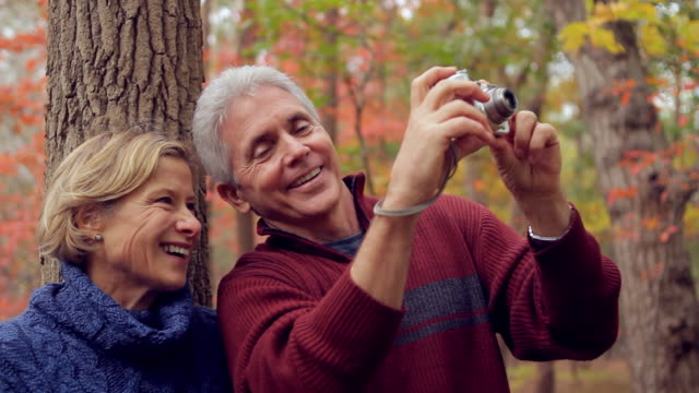 MS Mature couple taking pictures of fall color in the wood / Sea Bright, New Jersey, USA