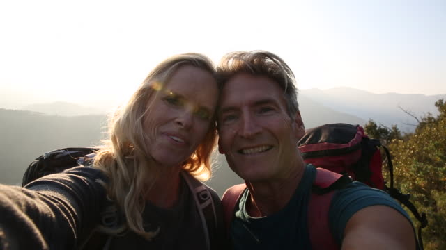 POV of mature couple taking selfie in mountain setting