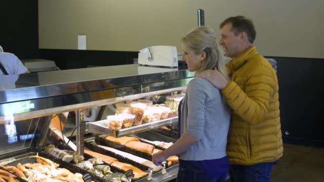 mature couple tasting salmon candy in a butcher shop - skåp med glasdörrar bildbanksvideor och videomaterial från bakom kulisserna