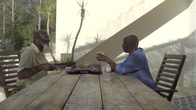 vídeos y material grabado en eventos de stock de a mature couple toast over breakfast - mesa de comedor