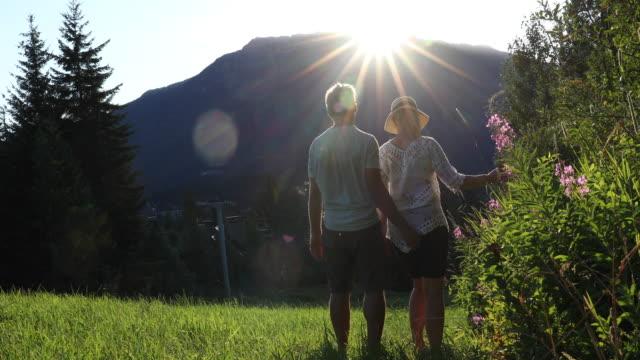 vidéos et rushes de mature couple traverse green mountain slope - activités de week end