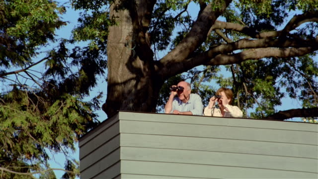 ms, la, mature couple using binoculars, standing on observation platform, usa, pennsylvania, solebury - バードウォッチング点の映像素材/bロール