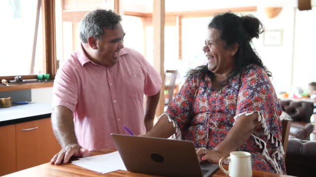 Mature couple using laptop and laughing