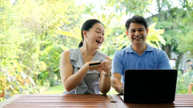 vidéos et rushes de couples matures utilisant l'ordinateur portatif pour payer des factures - credit card