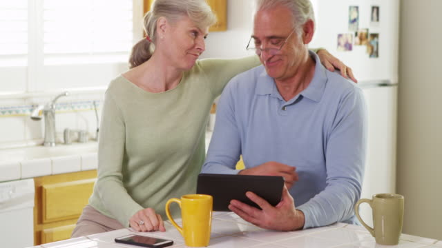 mature couple using tablet pad in kitchen - mature couple stock videos and b-roll footage
