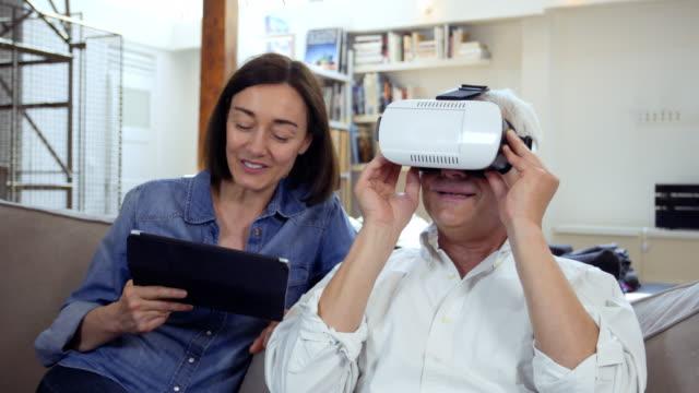vidéos et rushes de mature couple using virtual reality headset in living room - curiosité
