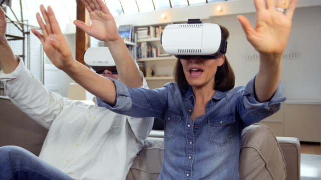 vídeos de stock, filmes e b-roll de mature couple using virtual reality headset in living room - 45 49 anos