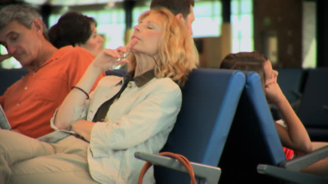 ms mature couple waiting for delayed flight at airport gate, appleton, wisconsin, usa - せっかち点の映像素材/bロール
