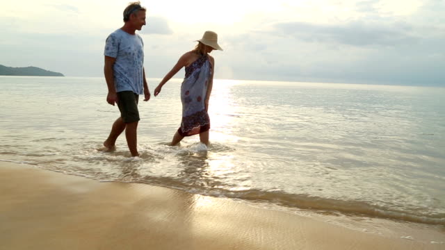 mature couple walk along beach as planes land above - mature couple stock videos & royalty-free footage