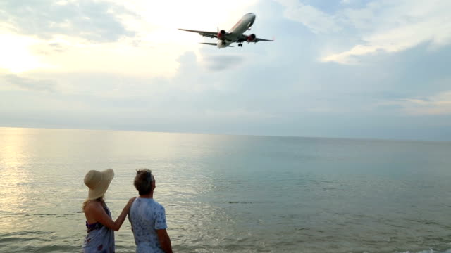 Mature couple walk along beach as planes land above