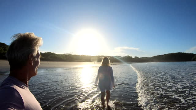 vídeos de stock e filmes b-roll de mature couple walk along beach at water's edge, into sunrise - water's edge