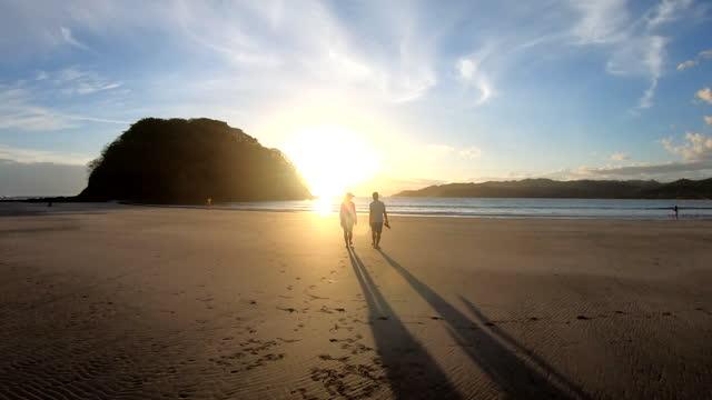 mature couple walk along beach towards surf, at sunrise - top garment stock videos & royalty-free footage
