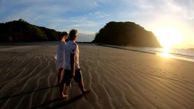 vídeos y material grabado en eventos de stock de mature couple walk along beach towards surf, at sunrise - scenics