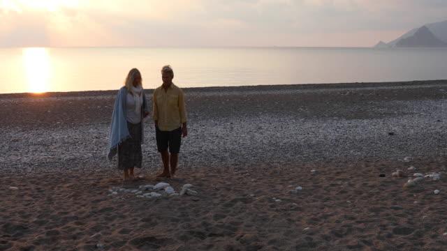 mature couple walk along empty beach at sunrise - asciugamano video stock e b–roll
