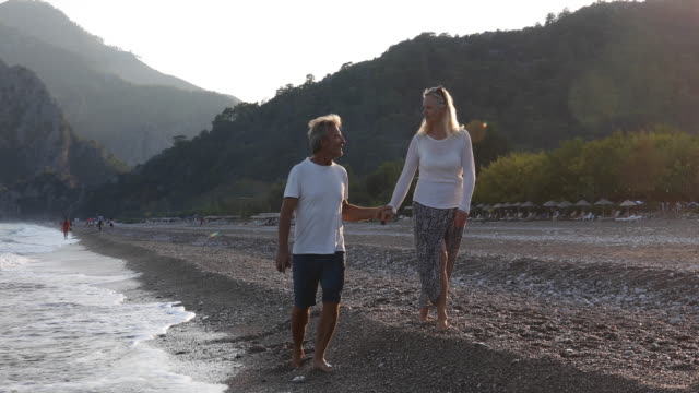 mature couple walk along empty beach at sunrise - shorts stock videos & royalty-free footage