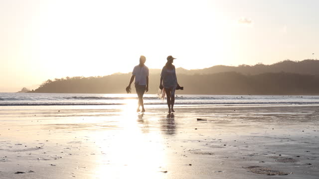 mature couple walk along empty beach, at sunrise - discovery stock videos & royalty-free footage