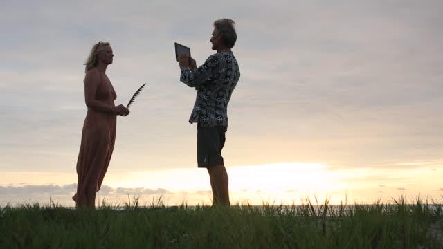 mature couple walk along grassy beach crest at sunrise, surf behind - オオハマガヤ属点の映像素材/bロール
