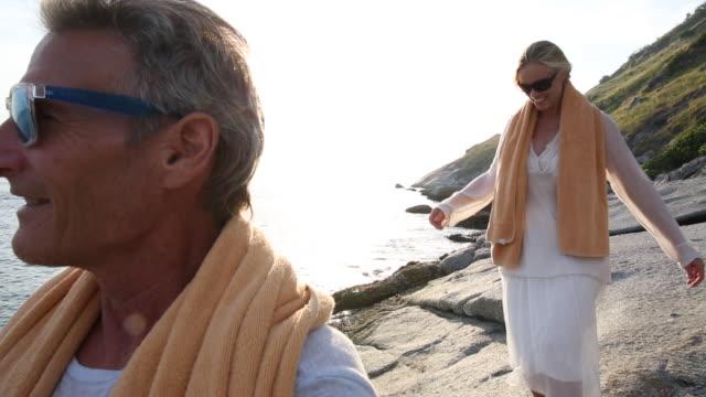 vídeos y material grabado en eventos de stock de mature couple walk along picturesque coastline, wearing towels - 55 59 años