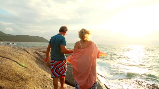 Mature couple walk along rock slabs above sea