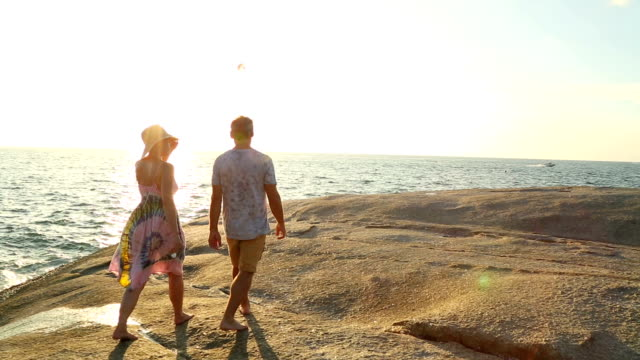 Mature couple walk along rock slabs above sea