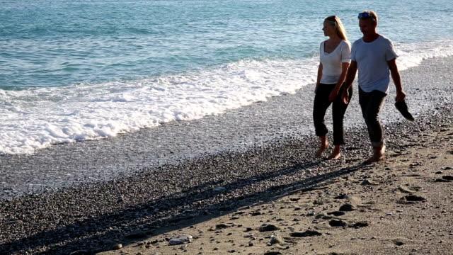 Mature couple walk along surf edge, talking