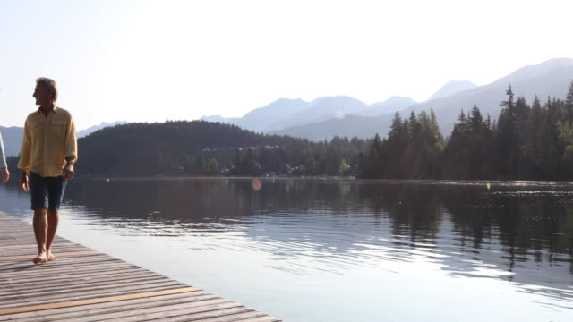 mature couple walk along wooden lake pier at sunrise - pier stock videos & royalty-free footage