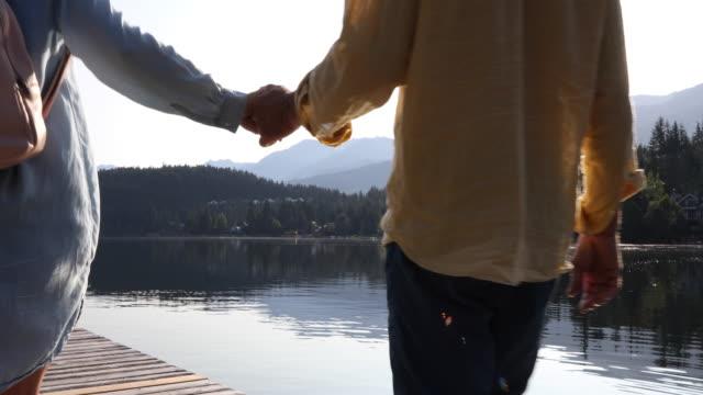 成熟したカップルは日の出に木製の湖の桟橋に沿って歩きます - distant点の映像素材/bロール