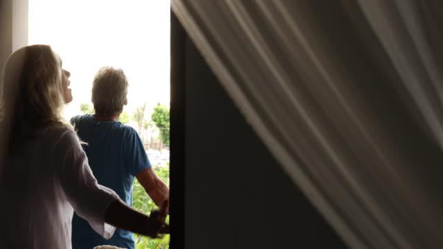 mature couple walk onto balcony of holiday villa - villa stock videos & royalty-free footage