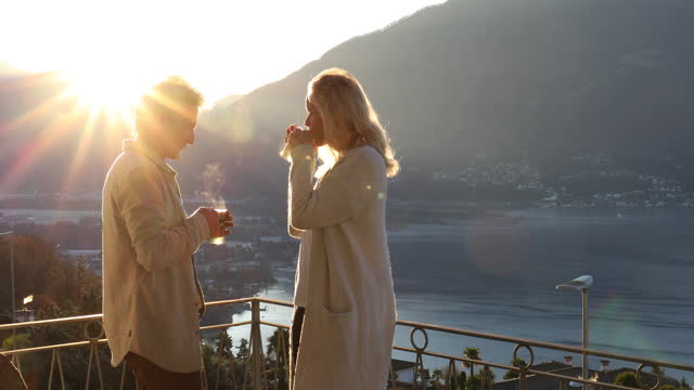 mature couple walk onto rooftop terrace at sunrise - standing water stock videos & royalty-free footage