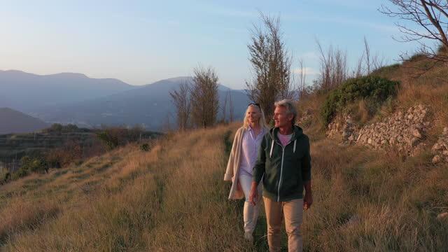 coppia matura a piedi attraverso aspre terreni agricoli terrazzati ammirando la vista dell'alba - giacca video stock e b–roll