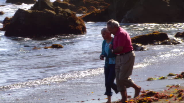 stockvideo's en b-roll-footage met ms, pan, mature couple walking and hugging in rocky beach, moonstone beach, cambria, california, usa - noordelijke grote oceaan