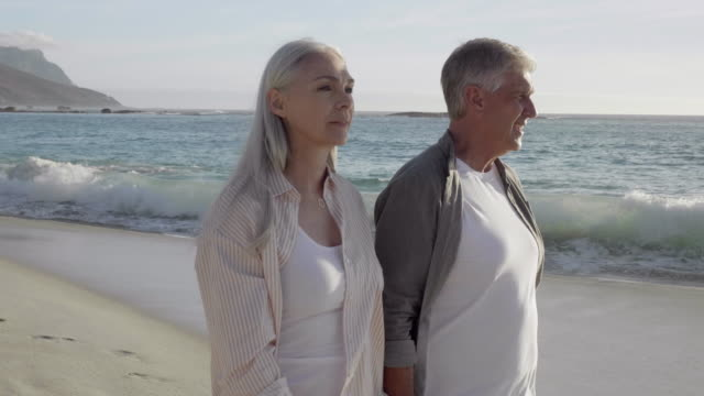vídeos y material grabado en eventos de stock de pareja madura caminando en la playa en verano - 50 59 años