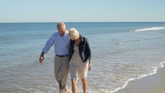 vídeos de stock, filmes e b-roll de ms ts mature couple walking on water / clinton, new jersey, usa - jaqueta jeans