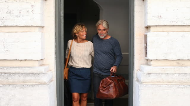 Mature couple walking out of appartment building with suitcases