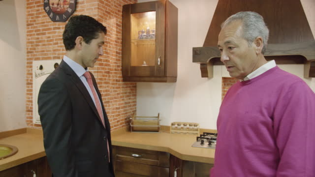 MS TS mature couple walking through display of traditional kitchen furniture, talking to salesman