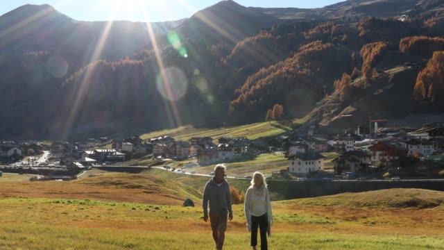 mature couple walks across mountain meadow, look out over village - eskapismus stock-videos und b-roll-filmmaterial