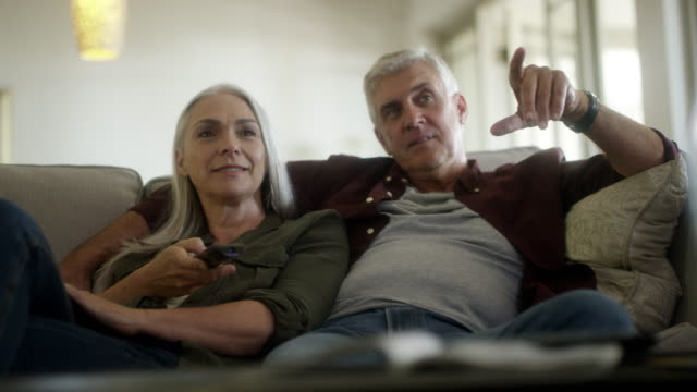 mature couple watching tv at home - mature couple stock videos & royalty-free footage