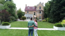 Mature couple with arms around each other looking at house and view of building exterior