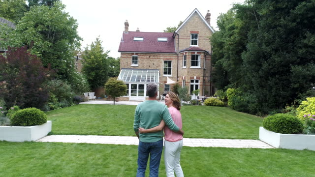 mature couple with arms around each other looking at house and view of building exterior - house stock videos & royalty-free footage