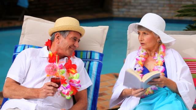 vídeos de stock, filmes e b-roll de mature couple with garlands chatting in deckchairs / cape town, western cape, south africa - espreguiçadeira