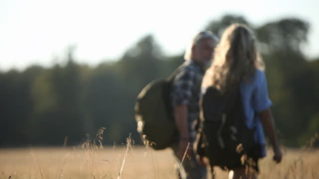 mature couple with rucksacks hiking in long grass - 熟年カップル点の映像素材/bロール